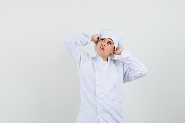Vrouwelijke chef-kok in wit uniform omklemd hoofd met handen