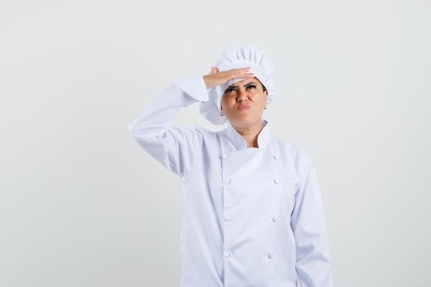 Vrouwelijke chef-kok in wit uniform op zoek naar boven met hand over de ogen