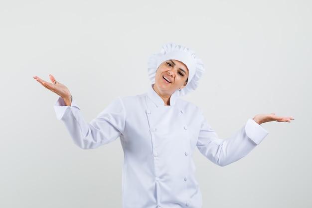 Vrouwelijke chef-kok in wit uniform schalen gebaar maken en op zoek blij