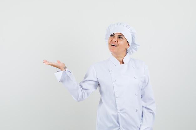 Vrouwelijke chef-kok in wit uniform spreidende palm opzij en hoopvol kijkt