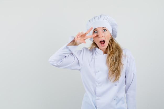 Vrouwelijke chef-kok in wit uniform v-teken dichtbij oog tonen en gek kijken