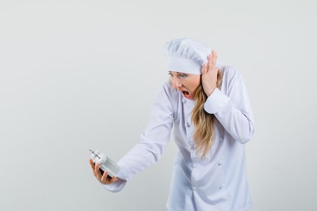 Vrouwelijke chef-kok in wit uniform wekker kijken en opgewonden kijken