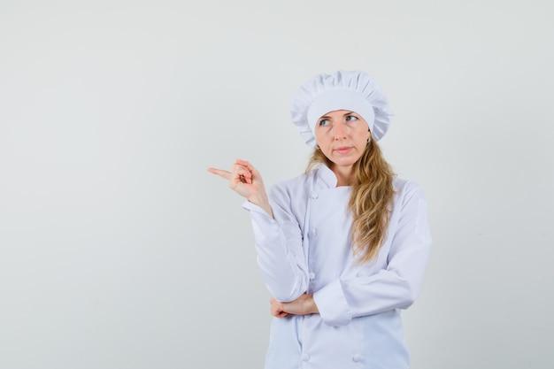 Vrouwelijke chef-kok in wit uniform wijst naar de kant en kijkt aarzelend