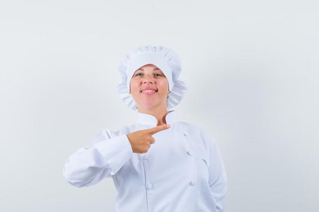 Vrouwelijke chef-kok in wit uniform wijst naar de rechterkant en kijkt zelfverzekerd