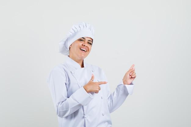 Vrouwelijke chef-kok in wit uniform wijst naar de zijkant en kijkt blij