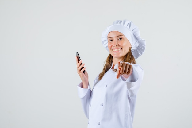 Vrouwelijke chef-kok in wit uniform wijzende vinger op camera met smartphone en op zoek vrolijk.