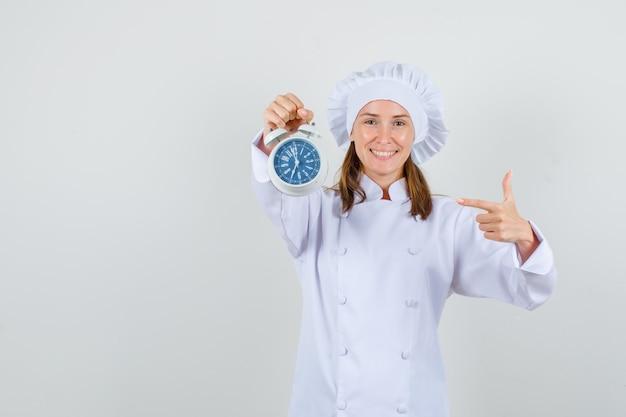 Vrouwelijke chef-kok in wit uniform wijzende vinger op wekker en vrolijk kijken