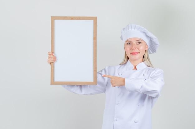 Vrouwelijke chef-kok in wit uniform wijzende vinger op wit bord en vrolijk kijken