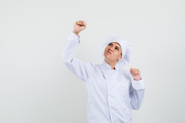 Vrouwelijke chef-kok in wit uniform winnaargebaar tonen en gelukkig kijken