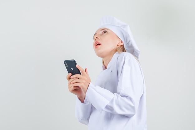 Vrouwelijke chef-kok in witte uniforme smartphone houden en denken.