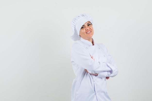 Vrouwelijke chef-kok in witte uniforme staande met gekruiste armen en blij kijken