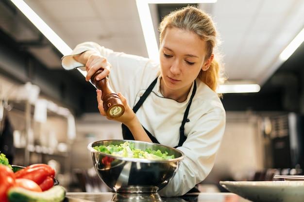 Vrouwelijke chef-kok kruiden salade