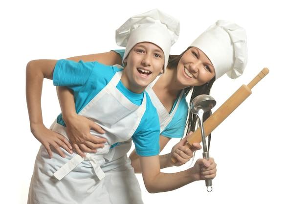 Vrouwelijke chef-kok met assistent die battledore en soeplepel vasthoudt