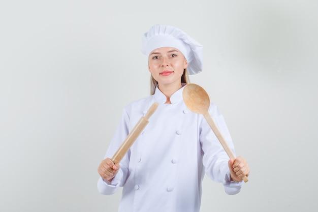 Vrouwelijke chef-kok met deegroller en houten lepel in wit uniform en op zoek vrolijk