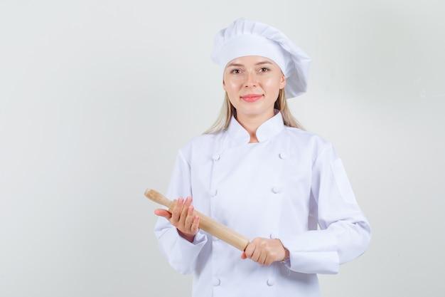 Vrouwelijke chef-kok met deegroller in wit uniform en op zoek vrolijk.