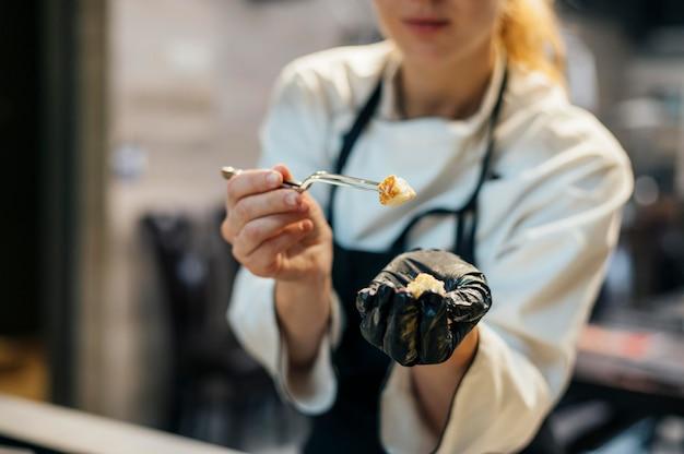Vrouwelijke chef-kok met handschoen die voedsel test als het wordt gekookt