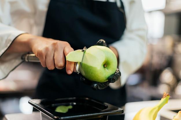 Vrouwelijke chef-kok met handschoen en schort die appelschil verwijderen