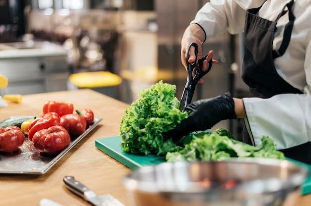 Vrouwelijke chef-kok met handschoen hakkende salade