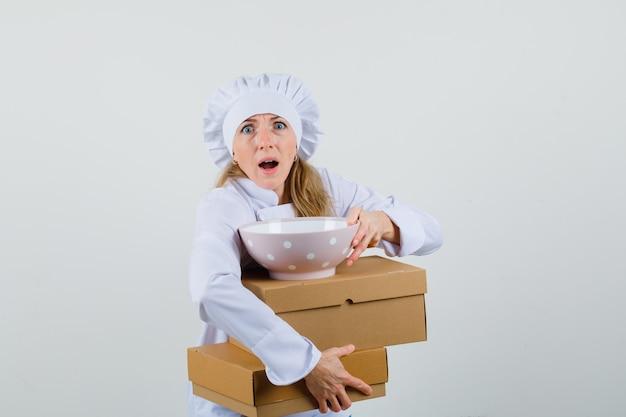 Vrouwelijke chef-kok met kom met kartonnen dozen in wit uniform