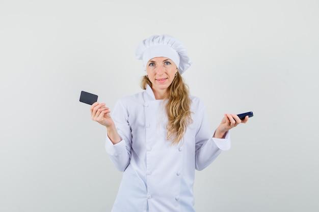 Vrouwelijke chef-kok met mobiel en kaart in wit uniform en op zoek optimistisch.