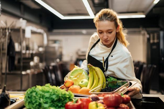Vrouwelijke chef-kok met schort en dienblad met fruit