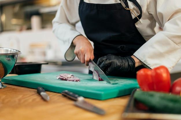 Vrouwelijke chef-kok met schort en handschoen hakkende groenten