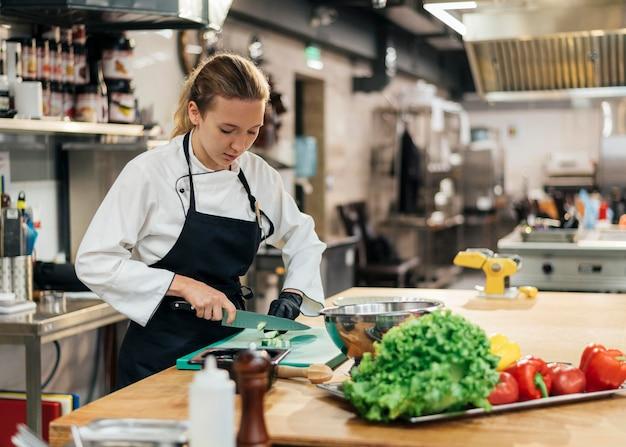 Vrouwelijke chef-kok met schort scherpe groenten