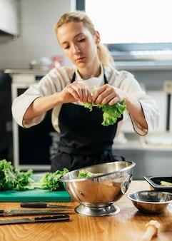Vrouwelijke chef-kok met schort scheuren salade in kom