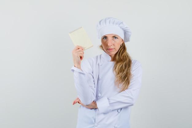 Vrouwelijke chef-kok met voorbeeldenboek in wit uniform en op zoek naar vertrouwen.
