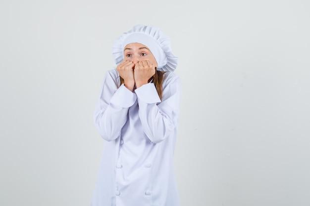 Vrouwelijke chef-kok met vuisten op de mond in wit uniform en bang op zoek. vooraanzicht.