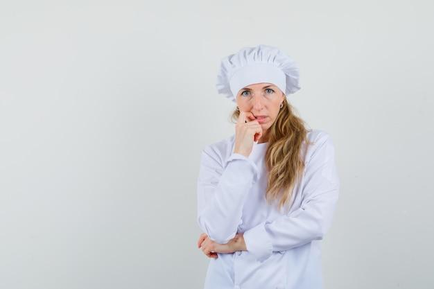 Vrouwelijke chef-kok permanent in denken pose in wit uniform en hulpeloos op zoek.