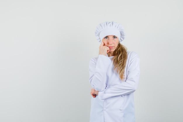 Vrouwelijke chef-kok permanent in denken pose in wit uniform en op zoek gericht.