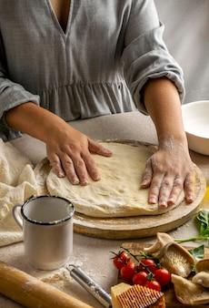Vrouwelijke chef-kok pizza deeg uitrekken