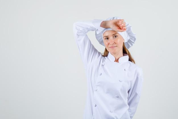 Vrouwelijke chef-kok poseren met arm op hoofd in wit uniform en op zoek blij
