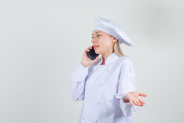 Vrouwelijke chef-kok praten over smartphone met hand teken in wit uniform
