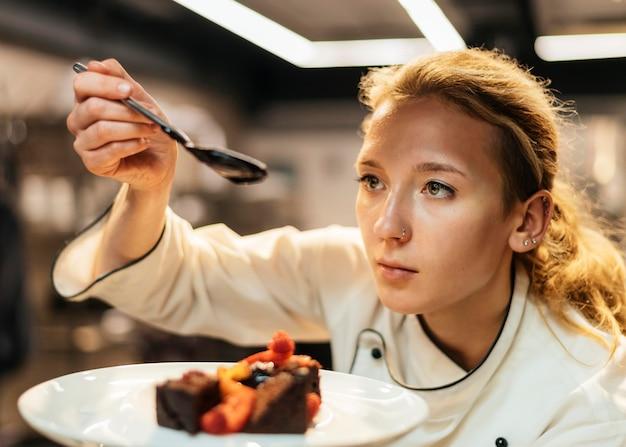 Vrouwelijke chef-kok saus over schotel zetten