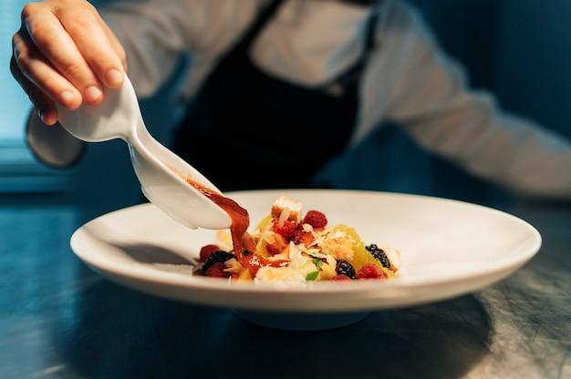 Vrouwelijke chef-kok saus toe te voegen aan schotel