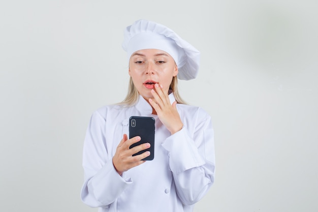Vrouwelijke chef-kok smartphone in wit uniform houden en verbaasd kijken