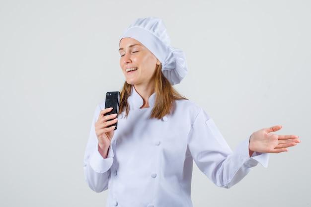 Vrouwelijke chef-kok smartphone met open hand in wit uniform te houden en op zoek vrolijk