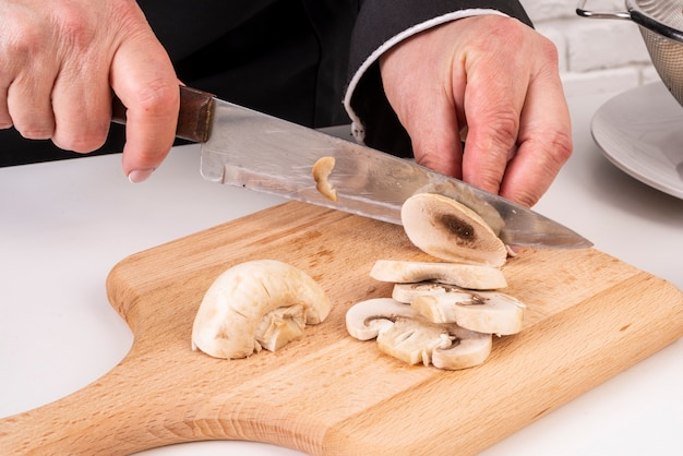 Vrouwelijke chef-kok snijden paddestoelen op snijplank