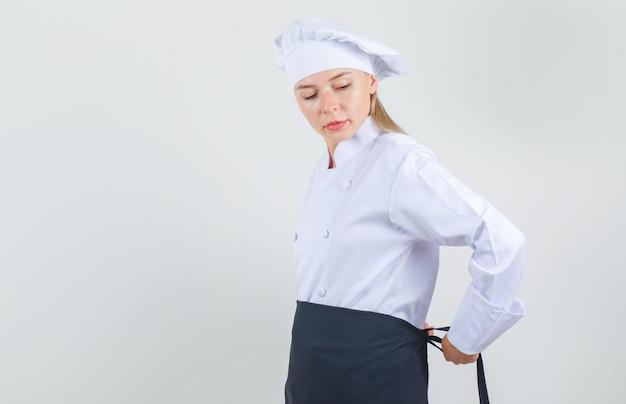 Vrouwelijke chef-kok vastbinden schort rond taille in wit uniform