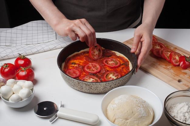 Vrouwelijke chef-kok voegt tomaten toe om zelfgemaakte pizza te maken.