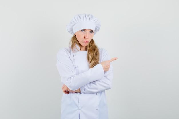 Vrouwelijke chef-kok wijst naar de kant in wit uniform en kijkt beledigd.