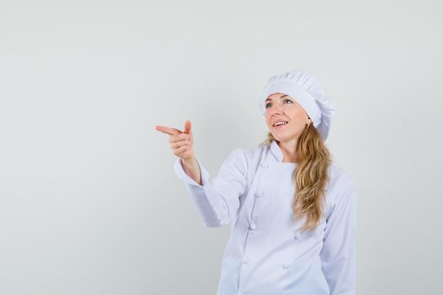Vrouwelijke chef-kok wijst naar de kant in wit uniform en kijkt vrolijk.