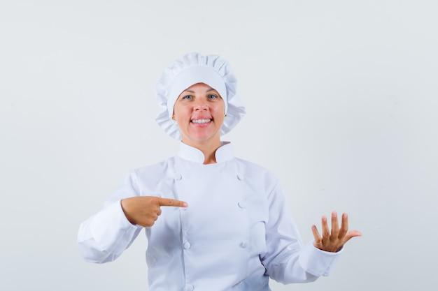 Vrouwelijke chef-kok wijzend op iets deed alsof hij in wit uniform werd vastgehouden en keek zelfverzekerd