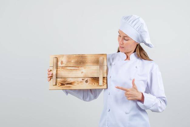 Vrouwelijke chef-kok wijzende vinger op houten dienblad in wit uniform