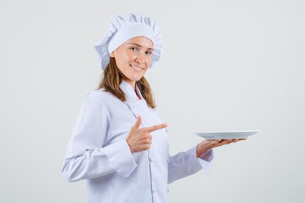 Vrouwelijke chef-kok wijzende vinger op plaat in wit uniform en blij kijken. .