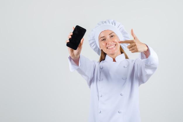 Vrouwelijke chef-kok wijzende vinger op smartphone in wit uniform en op zoek vrolijk. vooraanzicht.