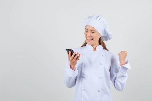 Vrouwelijke chef-kok winnaar gebaar tonen terwijl smartphone in wit uniform. vooraanzicht.
