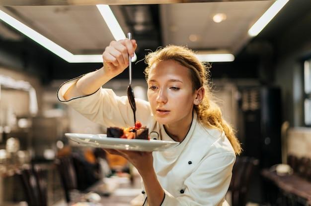Vrouwelijke chef-kok zorgvuldig saus gieten over schotel